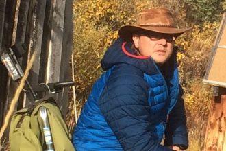 Mann mit Hut und blauer Daunenjacke